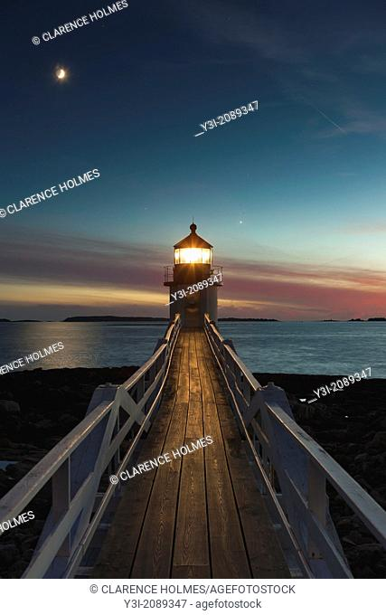 Marshall Point Lighthouse shines its beam into the evening sky to assist mariners entering and leaving Port Clyde Harbor in Port Clyde, Maine