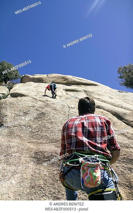 Climber securing a climber woman during climbing