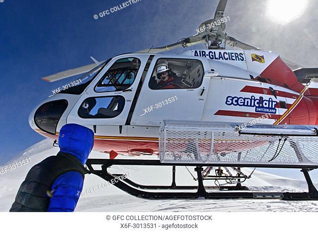 Heliskiing, helicopter Eurocopter AS 350B3 Ecureuil dropping skiers on peak Äbeni Flue, Berness Alps, Switzerland
