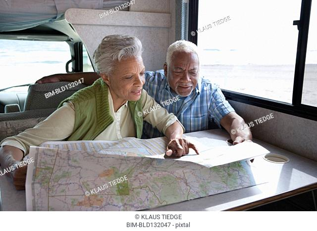 Mixed race Senior couple reading map in RV
