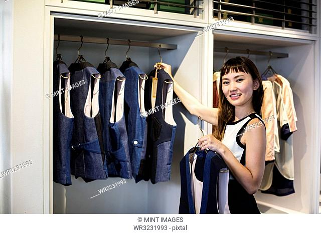 Japanese saleswoman standing in clothing store, hanging blue waistcoats on rail, smiling at camera