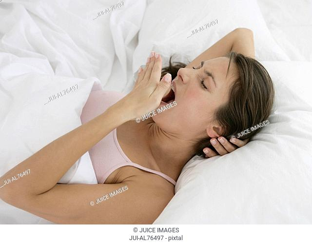 Portrait of a young woman yawning in bed