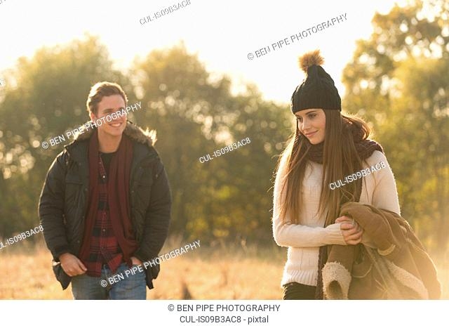 Young couple walking through field, smiling