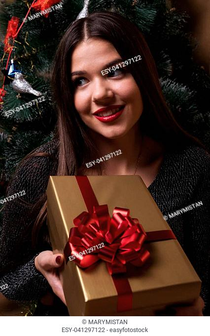 A girl is holding a gift, sitting under a Christmas tree
