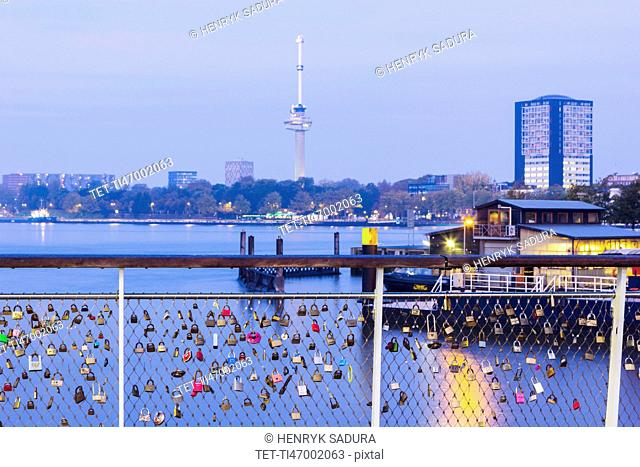 Netherlands, Rotterdam, Padlocks on railing with river in background