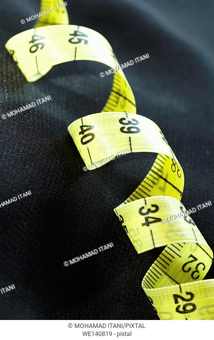 Yellow tape measure on a black background