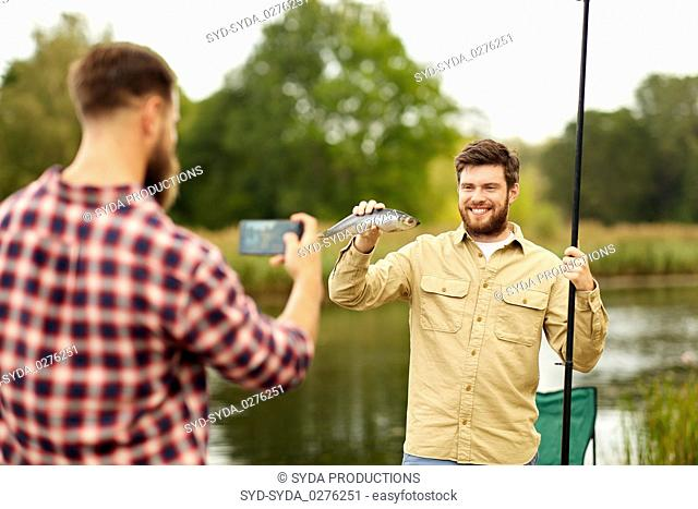 friend photographing fisherman with fish at lake