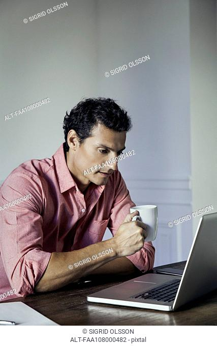 Man drinking coffee while using laptop computer