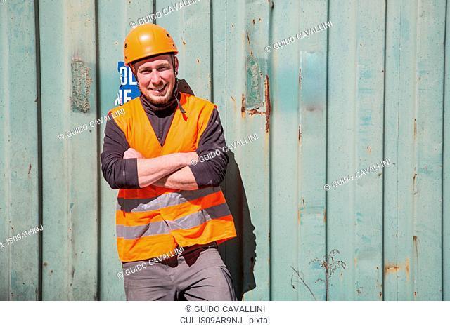 Portrait of worker wearing protective workwear in front of wooden door