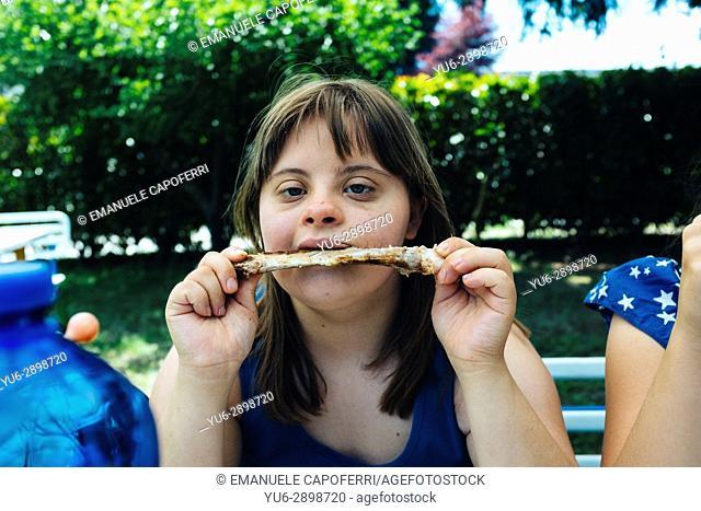Little girl eat pork ribs