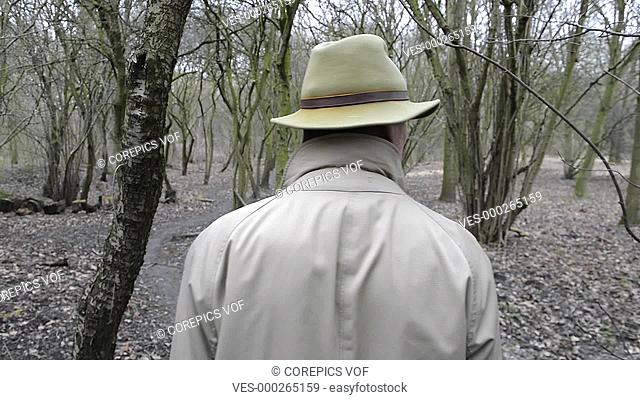 Man, wearing a khaki trench coat and a faded felt hat walking through damp, grey woods