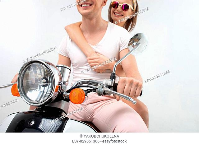 Lets remember this happy moment. Portrait of beautiful loving couple traveling by scooter. The girl is embracing her boyfriend with love