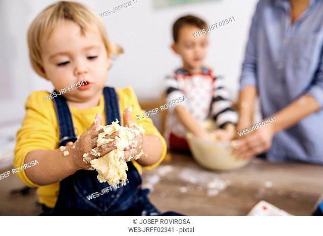 Toddler girl kneading dough with hers hands, close-up