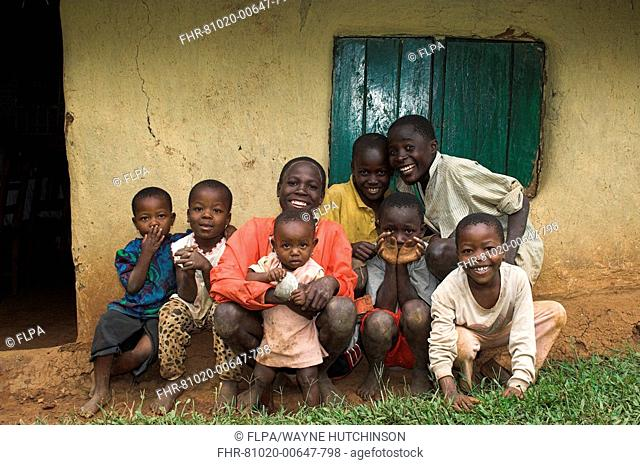 Group of smiling children, various ages, sitting outside hut, Western Kenya