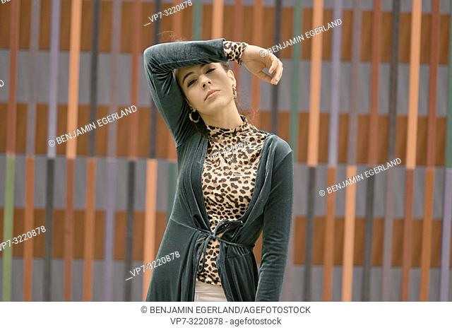 portrait of sensual fashionable woman, tired sleepy mood, bleary, individual style, in front of geometrical line pattern, in Munich, Germany