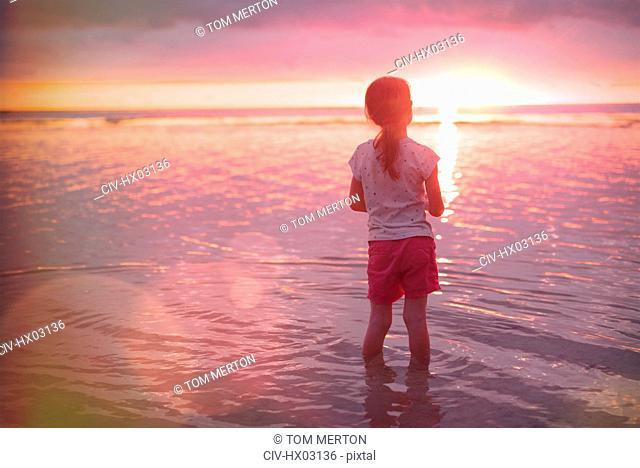 Pensive girl wading in ocean on tranquil sunset beach