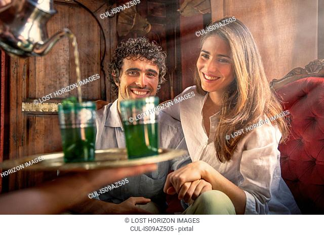 Young couple in riad being served drinks on tray, Marrakesh, Morocco