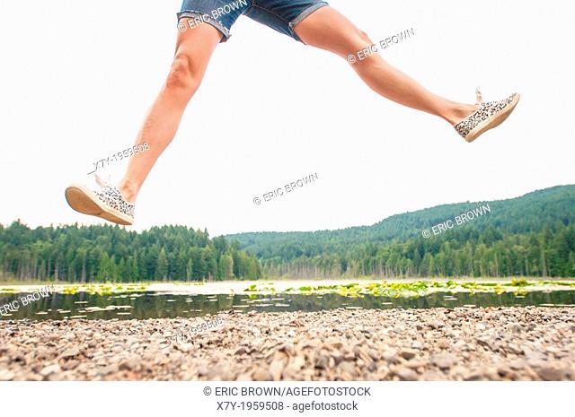 A woman jumping beside a lake in Bowen Island, British Columbia, Canada