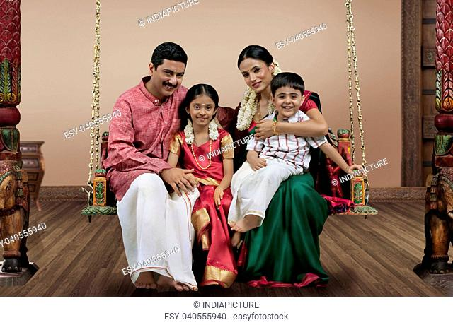 Portrait of a South Indian family sitting on a jhula
