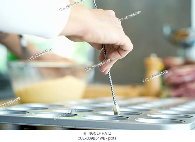Chef brushing oil onto baking tray, close-up