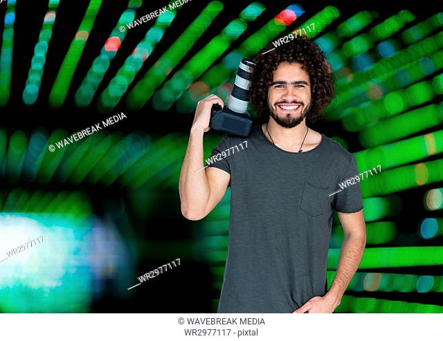 happy photographer with the camera rest on his shoulder. Green blurred lights behind