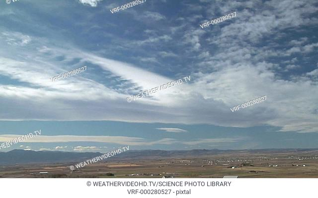 Timelapse footage of unusual mountain wave clouds. The prominent bar of cloud across centre marks the crest of a standing wave
