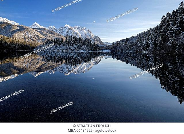 The reservoir Krün in the evening light. In the background the snow-covered western Karwendelgebirge (mountains) with mirroring in the water