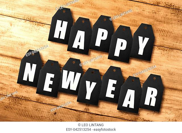 Happy New Year text in tag sale on wooden background. Happy New Year 2019