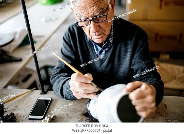 Senior man decorating ceramic vase in his spare time