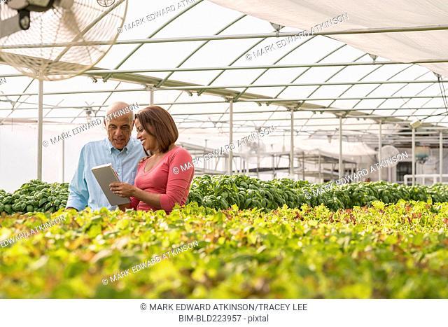 Couple reading clipboard near green plants in greenhouse