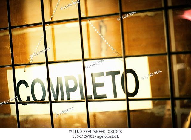 Notice of 'completo' (No Vacancies) hung behind a door of a business in Granada, Andalucia, Spain