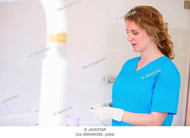 Dental nurse wearing scrubs and protective gloves preparing dental equipment