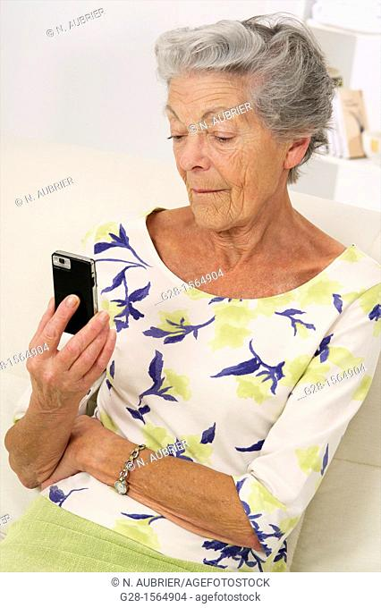 Senior woman holding her phone and reading a message