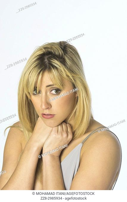 Sad beautiful blonde woman looking away against a white background