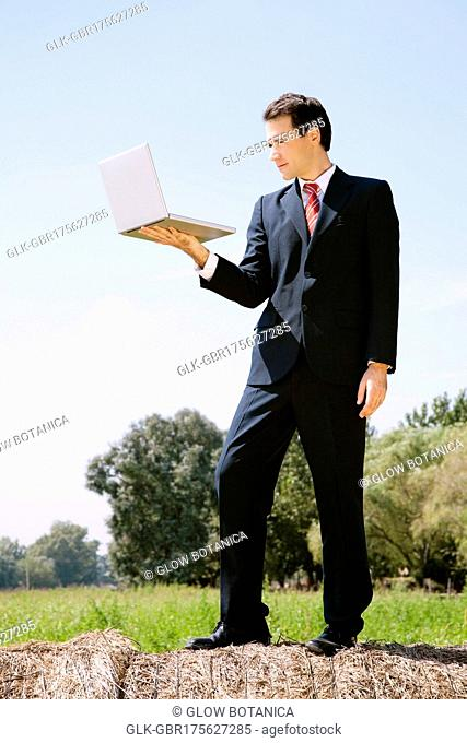 Businessman holding a laptop on a hay bale