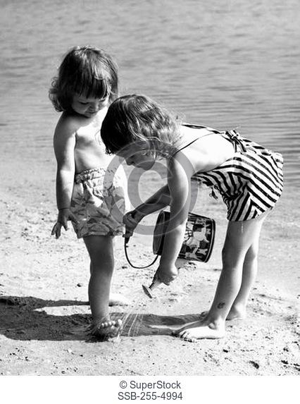 Girl pouring water on the foot of another girl on the beach