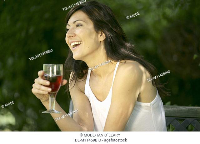 A woman sitting in the garden holding a glass of wine
