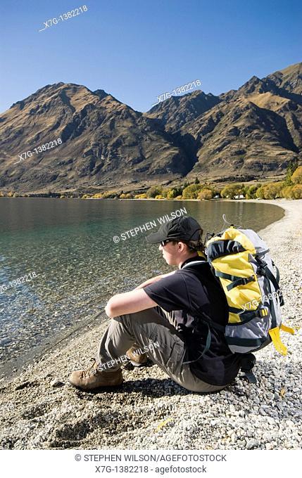 Young hiker sat on the shore at Glendhu Bay gazing out at Lake Wanaka, South Island of New Zealand