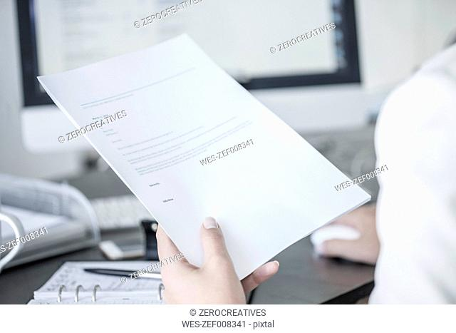 Close-up of woman at desk holding a document