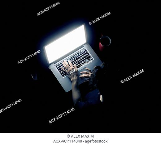 Woman at a desk with a laptop computer with a glowing screen isolated on black background