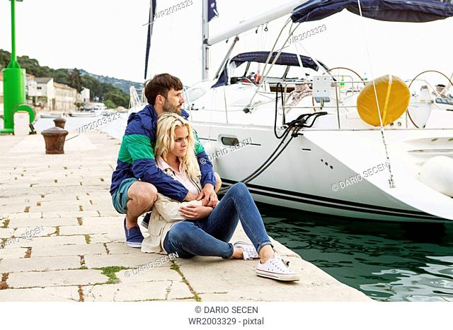 Young couple relaxing on pier, Adriatic Sea