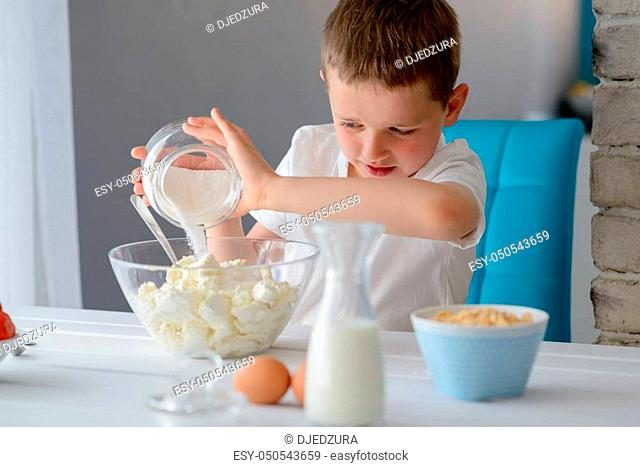 7 year old boy adding sugar to cottage cheese in a bowl. Prepares mini cheesecakes with strawberries