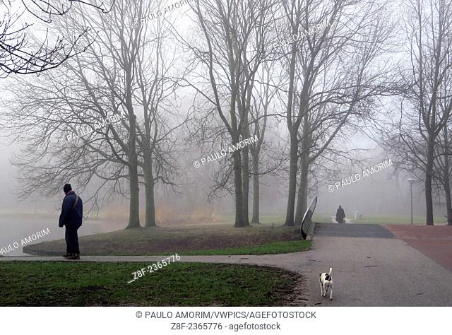 People at Rembrandt Park during a dense fog covering the city of Amsterdam in Netherlands
