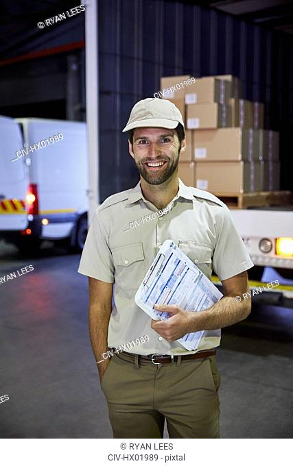 Portrait smiling truck driver worker with clipboard at distribution warehouse loading dock