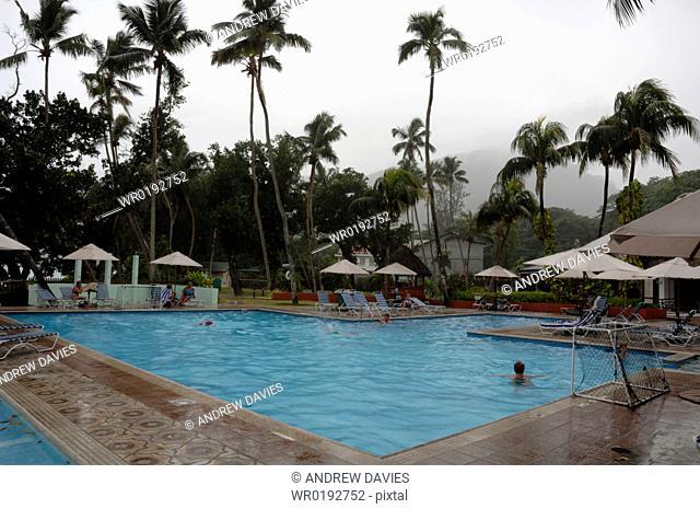 Swimming pool at Berjaya Beau Vallon Hotel during rain storm, Mahe, Seychelles, Indian Ocean