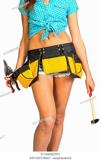 Woman wearing shirt. shorts and tool belt, holding tin snips and hammer, close up, isolated on white background