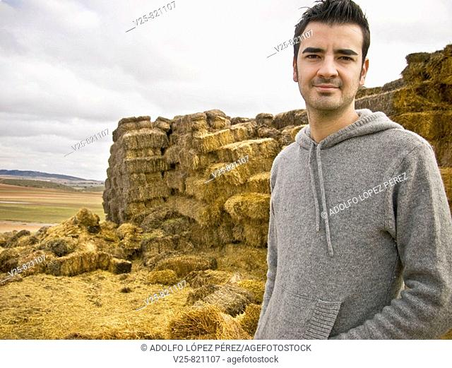 Young shepherd, straw bales in background. Albacete province, Castile-La Mancha, Spain