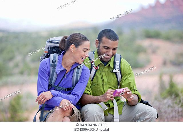 Hiking couple reading message on smartphone, Sedona, Arizona, USA