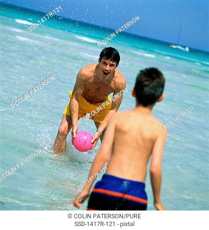 Father and his son playing with a ball on the beach