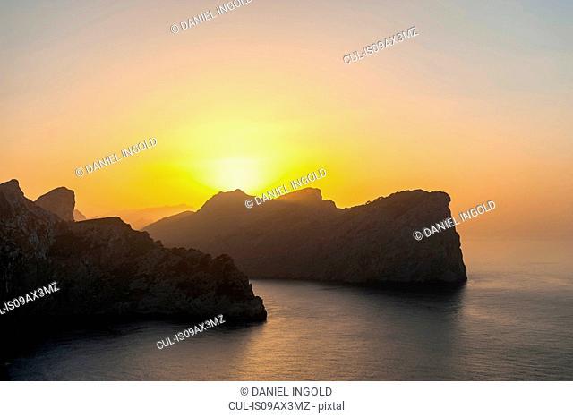 Sun setting behind rock formation in sea, Mallorca